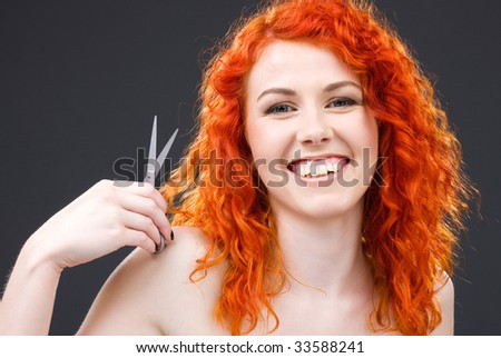 picture of lovely redhead with scissors over grey - stock photo