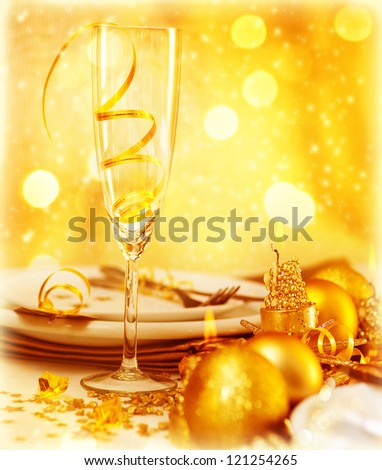 Picture of luxury festive table setting, closeup image of beautiful white utensil decorated with golden shiny balls and candle on blur glowing background, New Year eve, Christmas holiday dinner party - stock photo
