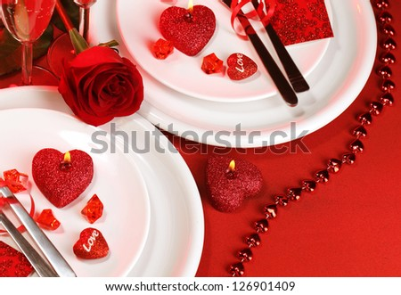 Picture of luxury festive table setting, white plate on red tablecloth served with silverware cutlery and decorated with fresh rose flower and heart-shaped candles, Valentine day, love concept - stock photo