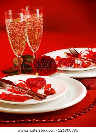 Picture of luxury table setting, romantic dinner, white festive utensil served with silverware and glasses for champagne, decorated with red rose flower and candles, Valentine day, love concept - stock photo