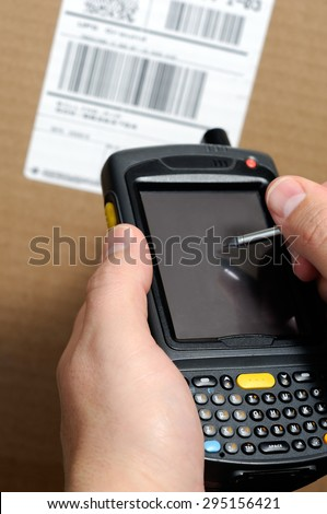 Picture of male hands using a hand held barcode scanner Enterprise Digital Assistant computer to take inventory with a UPC box label. - stock photo