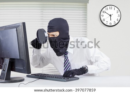 Picture of male robber wearing mask and looking for information with a magnifier on the computer in office - stock photo