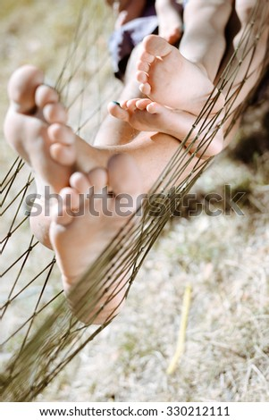 Picture of man and little child barefoot resting in countryside. Closeup of happy family's feet in hammock on sunny summer day background. - stock photo