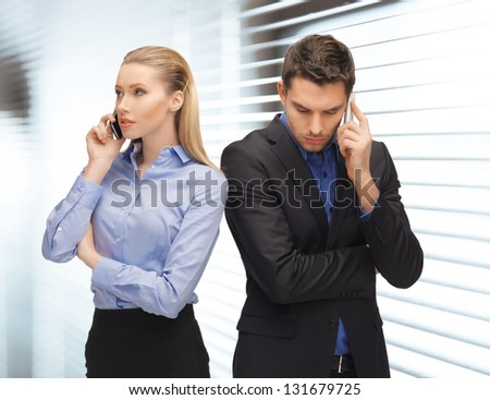 picture of man and woman with cell phones - stock photo