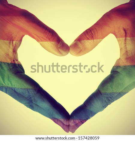 picture of man hands forming a hear patterned with the gay pride flag, with a retro effect - stock photo