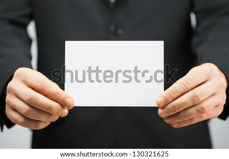 picture of man in suit holding blank card.