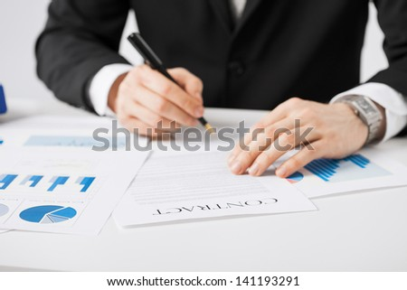 picture of man in suit signing contract - stock photo