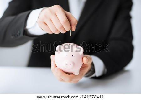 picture of man putting coin into small piggy bank - stock photo
