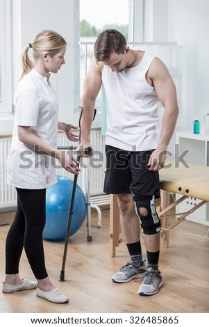 Picture of man with knee orthosis in physiotherapy room - stock photo