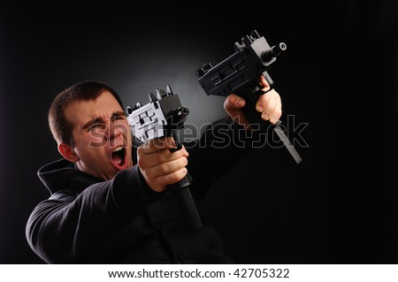 Picture of man with pair of uzi - stock photo
