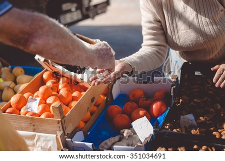 Picture of marketplace with different fruits. Buyer's and seller's hands on colorful background outdoors - stock photo