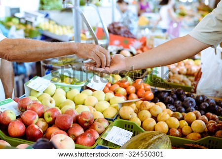 Picture of marketplace with different fruits. Buyer's hand and seller's hand on blurred colorful background.