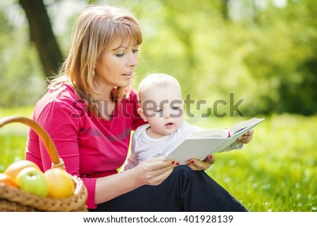 Picture of mature woman with son sitting down on green grass field and read fairytale in park. - stock photo