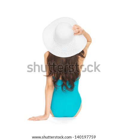 picture of model sitting in swimsuit with hat. - stock photo
