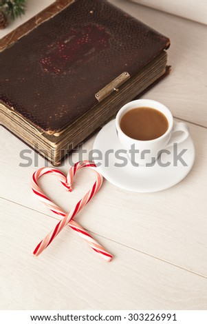 Picture of morning cup of coffee, album and candy cane - stock photo