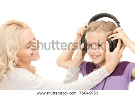 picture of mother and little girl with headphones - stock photo