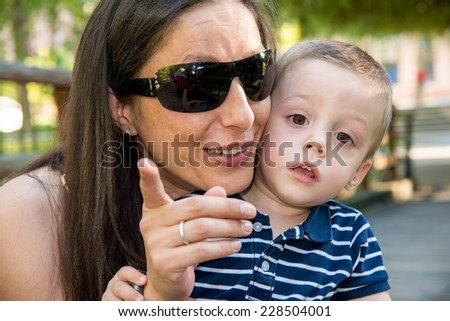 picture of mother and son looking and pointing at camera