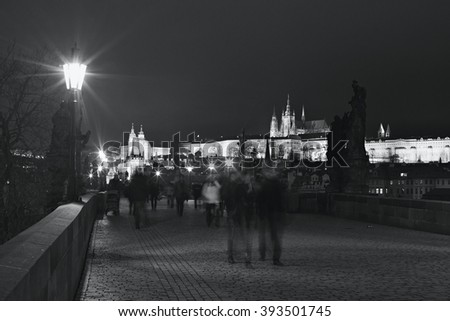 Picture of night Charles bridge in Prague with not sharpened turists walking on. Charles bridge is one of most beautiful examples of gothic architecture in Czech Republic. Under unesco - stock photo