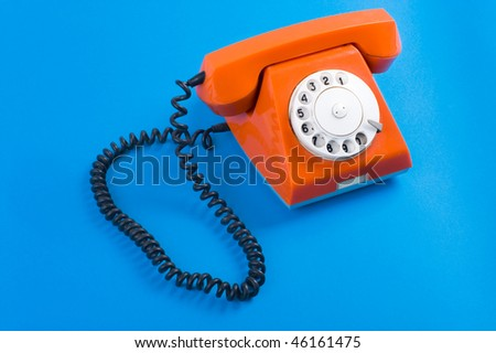 Picture of old fashioned telephone over blue background - stock photo