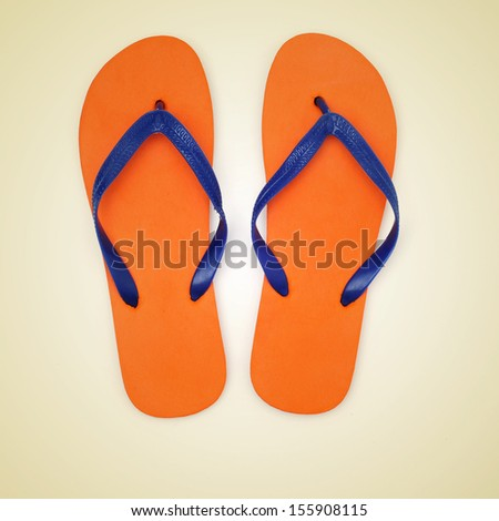 picture of orange and blue flip-flops on a beige background, with a retro effect - stock photo
