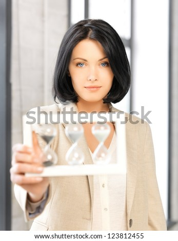 picture of pensive businesswoman with sand glass - stock photo