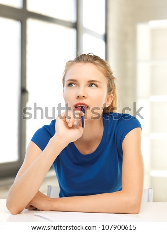 picture of pensive teenage girl with pen and paper - stock photo