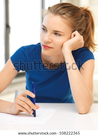 picture of pensive teenage girl with pen and paper