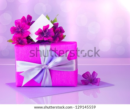 Picture of pink gift box with purple silk ribbon, beautiful violet wild flowers bouquet, white blank greeting card, beautiful romantic still life, blur background, happy mothers day, reflection - stock photo