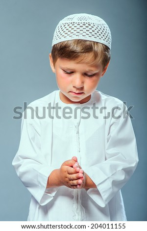 Picture of praying Middle eastern boy. - stock photo