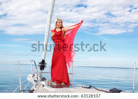 picture of pretty young woman in red dress posing on the bow yacht - stock photo