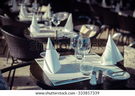 Picture of restaurant's interior in brown and white. Rows of tables and chairs with beautiful glass and dishwares on blurred indoor background. - stock photo