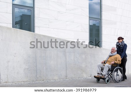 Picture of retired man with paralysis and nice carer - stock photo