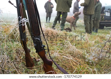 Picture of rifles in front hunters with dog. - stock photo