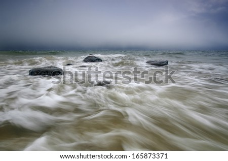 Picture of rocks flooded by coming wave.  - stock photo