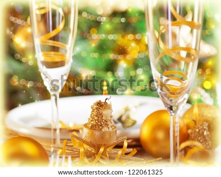 Picture of romantic holiday dinner in restaurant, Christmastime table setting with golden festive decorations, luxury white plate served with glass for champagne, beautiful adorned Christmas tree - stock photo