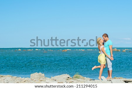 Picture of romantic young couple by the sea. Space for text.