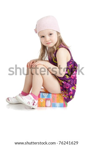 Picture of smiling little girl in a pink hat sitting on a gift - stock photo