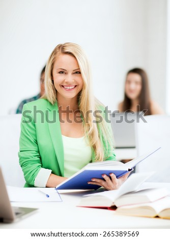 picture of smiling young woman reading book at school - stock photo