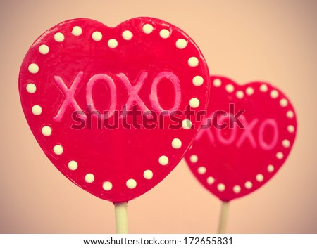 picture of some heart-shaped lollipops with the text XOXO, hugs and kisses, written in them, with a retro effect - stock photo