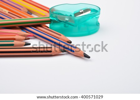 Picture of some pencils with stripes of different colors and a green pencil put in a pencil sharpener on a white background. Selective focus - stock photo
