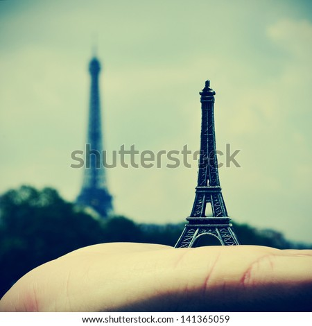 picture of someone holding a reproduction of the Eiffel Tower with the real Eiffel Tower in the background, in Paris, France, with a retro effect - stock photo
