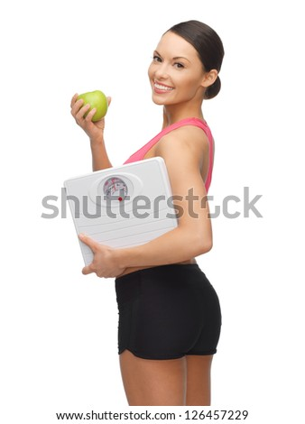 picture of sporty woman with apple and weight scale - stock photo