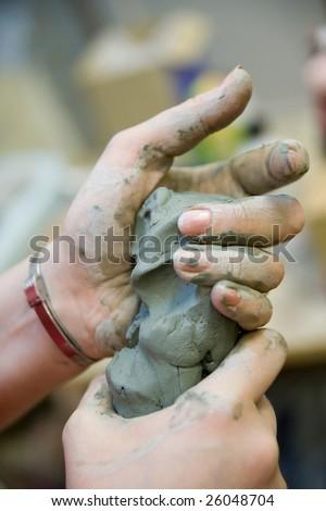 Picture of squeezing clay hands.
