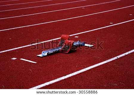 Picture of starting blocks placed on one the lanes. - stock photo