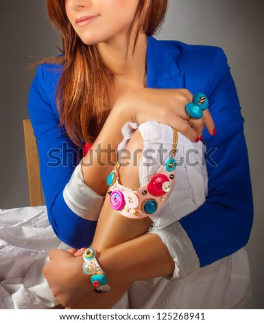 Picture of stylish woman wearing fashionable colorful clothes, pretty girl wearing gorgeous accessories, luxury jewelry, blue jacket and white dress, beautiful necklace and rings, beauty and vogue - stock photo