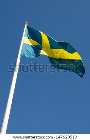 Picture of Swedish flag waving in the wind, on a blue sky  Picture of Swedish flag waving in the wind, on a blue sky - stock photo