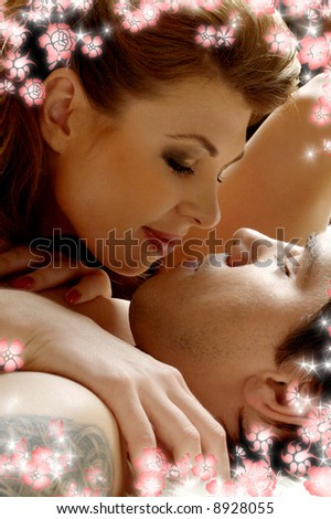 picture of sweet couple cuddling in bed with flowers