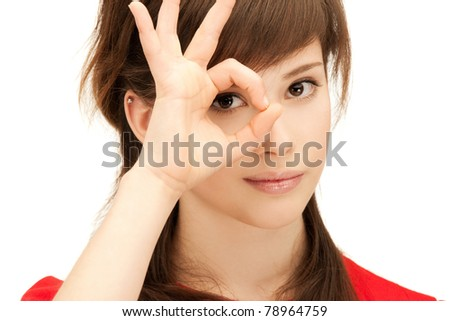 picture of teenage girl looking through hole from fingers - stock photo