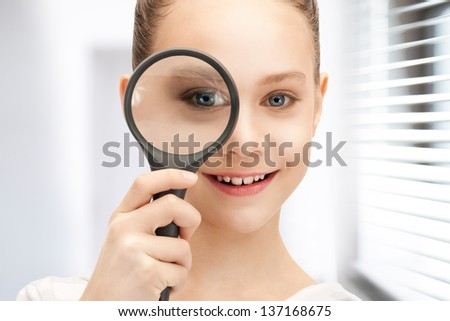 picture of teenage girl with magnifying glass - stock photo