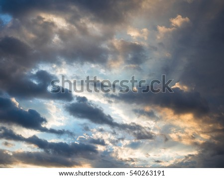 Picture of the sunset cloudy sky reflecting orange sun rays. Background of the still blue sunset sky with sun rays reflecting from the clouds.